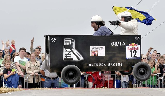 Competitors race down a big stockpile in a homemade coal lorry soapbox racer in Herten, Germany, on July 14, 2013. About 40,000 spectators climbed the 220 meters mine pile in the center of the Ruhr valley to watch the Red Bull soapbox fun race. (Photo by Martin Meissner/Associated Press)