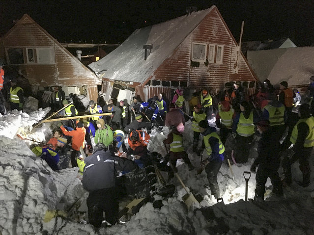 Search and rescue crews work after an avalanche hit several houses in Longyearbyen, Norway, Saturday December 19. 2015. It is unclear about the number of people caught in the avalanche but authorities are calling for volunteers with shovels to help in the search to locate victims. (Photo by NTB scanpix via AP Photo)