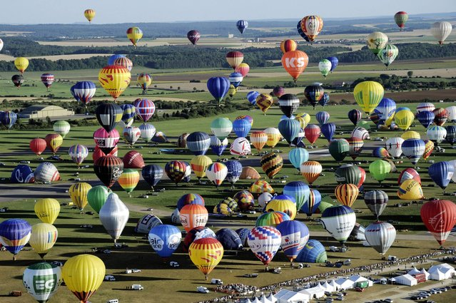 """Over 400 hot-air balloons take off in Chambley-Bussieres, eastern France, on Wednesday, July 31, 2013 in an attempt to set a world record for collective taking-off during the event """"Lorraine Mondial air ballons"""", an international hot-air balloon meeting. (Photo by Alexandre Marchi/AP Photo/L'est Republicain)"""