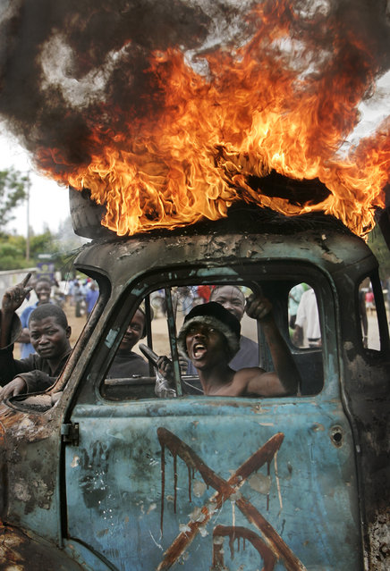 A Kenyan man sits in the cab of a destroyed truck used as a makeshift roadblock while a tyre burns on the roof, as he and others enforce the roadblock, during post-election violence in Kisumu, Kenya, Tuesday, January 29, 2008. (Photo by Ben Curtis/AP Photo)