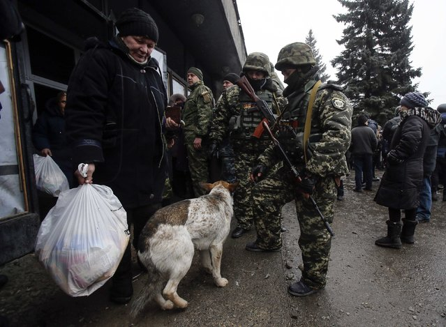A woman carries a bag with humanitarian aid as Ukrainian servicemen play with a dog in front of a delivery point in the government forces-controlled town of Debaltseve, Donetsk region February 6, 2015. (Photo by Maxim Shemetov/Reuters)