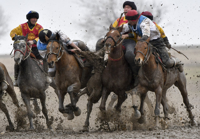 Riders compete during a kok boru, also called ulak tartysh, a traditional game in which players on horseback manoeuvre with a goat's carcass and score by putting it into the opponents' goal outside Sokuluk village, 20 km (12,5 miles) west of Bishkek, Kyrgyzstan, Tuesday, March 30, 2021. (Photo by Vladimir Voronin/AP Photo)