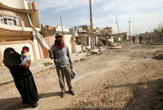 Displaced Iraqis leave their house in the frontline neighbourhood of Intisar, eastern Mosul November 27, 2016. (Photo by Mohammed Salem/Reuters)