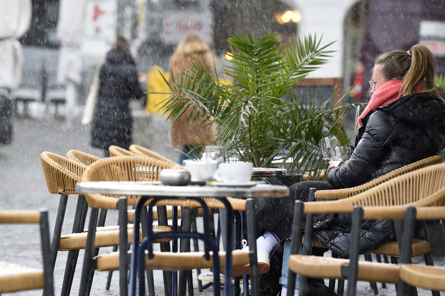 A woman takes a drink outside at a cafe during a sleet shower in Saarbruecken, western Germany, on April 6, 2021, as the border state of Saarland on Tuesday partially reopened during the ongoing coronavirus (Covid-19) pandemic. Germans in the tiny border state of Saarland returned to cafes, cinemas and cultural venues on April 6, even as the rest of the country faces tighter coronavirus restrictions amid rising case numbers. (Photo by Jean-Christophe Verhaegen/AFP Photo)