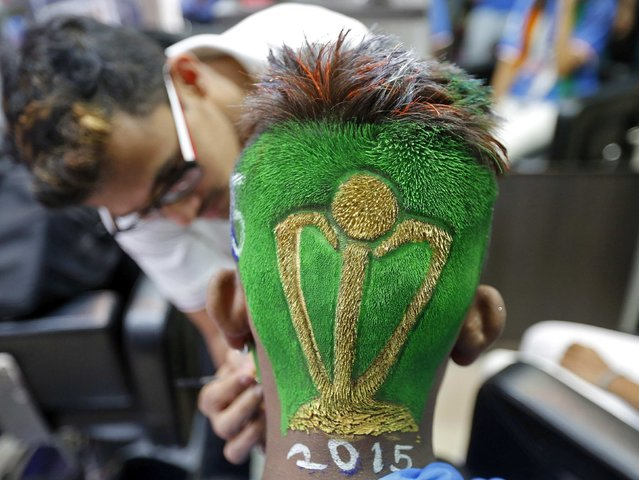 A cricket fan is pictured after having his hair trimmed into the shape of a Cricket World Cup trophy at a saloon during a promotional event in Mumbai February 12, 2015. The Cricket World Cup is jointly hosted by Australia and New Zealand and takes place from February 14. (Photo by Shailesh Andrade/Reuters)