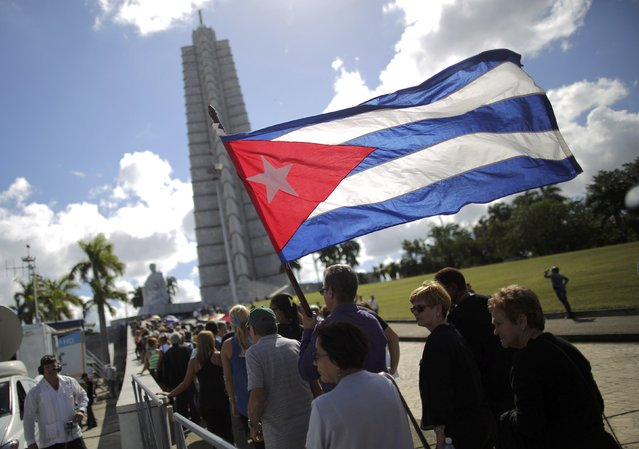 A man carries a Cuban flag as he and others march in tribute to Cuba's late President Fidel Castro at Revolution Square in Havana, Cuba, November 28, 2016. (Photo by Carlos Barria/Reuters)