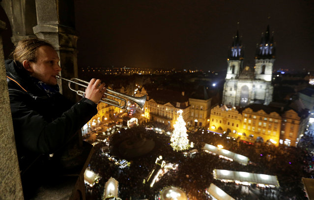 A man plays a trumpet from the Old Town Hall Tower as a Christmas tree is illuminated at the Old Town Square in Prague, Czech Republic, November 26, 2016. (Photo by David W. Cerny/Reuters)