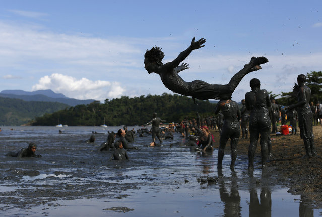 "A man jumps into the mud during the traditional ""Bloco da Lama"" or ""Mud Block"" carnival party, in Paraty, Brazil, Saturday, February 14, 2015. (Photo by Leo Correa/AP Photo)"