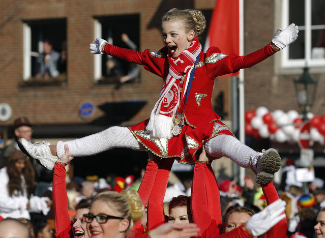 A young girl is lifted during the traditional Rose Monday carnival parade in Duesseldorf, Germany, Monday, February 16, 2015. (Photo by Frank Augstein/AP Photo)