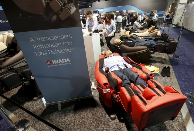 Attendees relax in Inada massage chairs during the 2016 CES trade show in Las Vegas, Nevada January 8, 2016. (Photo by Steve Marcus/Reuters)