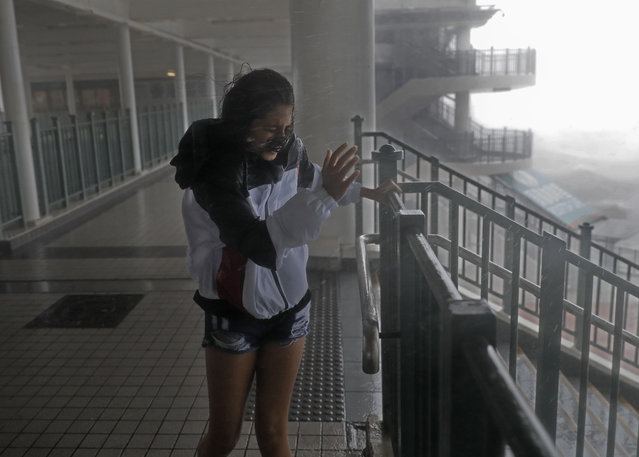 A girl stands against strong wind caused by Typhoon Mangkhut at a pier on the waterfront of Victoria Habour Hong Kong, Sunday, September 16, 2018. Hong Kong and southern China hunkered down as strong winds and heavy rain from Typhoon Mangkhut lash the densely populated coast. The biggest storm of the year left at least 28 dead from landslides and drownings as it sliced through the northern Philippines. (Photo by Vincent Yu/AP Photo)