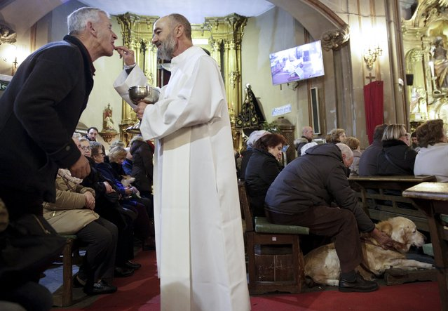 A man takes communion next to a man with his dog during a mass inside San Anton Church in Madrid, Spain, January 17, 2016. (Photo by Andrea Comas/Reuters)