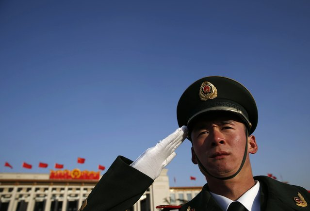 A paramilitary policeman salutes outside the Great Hall of the People after the opening session of Chinese People's Political Consultative Conference (CPPCC) at Tiananmen Square in Beijing March 3, 2015.  REUTERS/Kim Kyung-Hoon