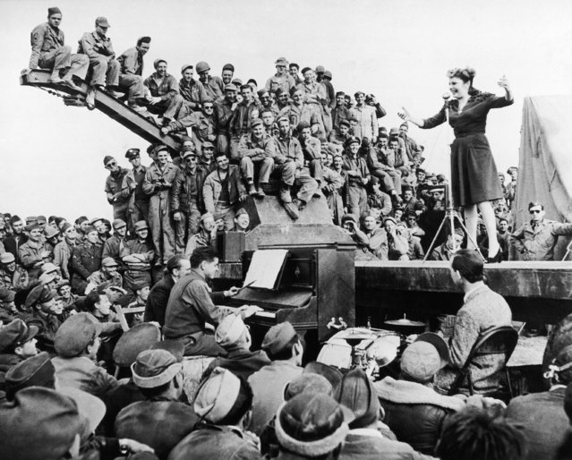 Flinging wisecracks, and singing hot songs from the home front in the good old U.S.A., Martha Raye, comedy actress, entertains men of the U.S. Army 12th Air Force on a makeshift stage on the edge of the Sahara Desert in North Africa, March 3, 1943. Some of these soldiers had just returned from a tough assignment to bomb bizerte, Tunisia. Martha was one of four American girls who toured the fighting front. (Photo by AP Photo)