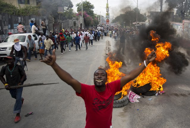 Demonstrators walk past a burning barricade during a street protest after it was announced that the runoff Jan. 24, presidential election had been postponed, in Port-au-Prince, Haiti, Friday, January 22, 2016. (Photo by Dieu Nalio Chery/AP Photo)