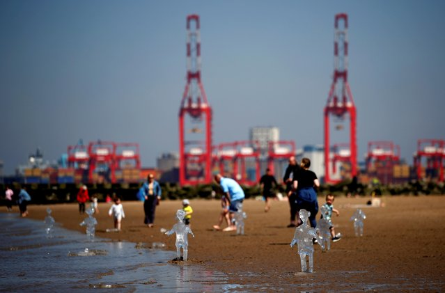 Ice sculptures of children created by Sand in Your Eye to highlight the importance of COP26, the global climate conference, are seen at New Brighton Beach on the Wirral peninsular in New Brighton, Britain on May 31, 2021. (Photo by Jason Cairnduff/Reuters)