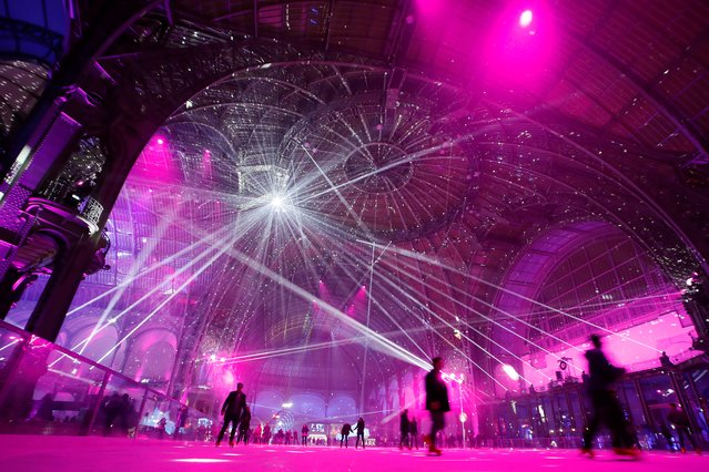 People skate on the ice skating rink hosted at the glass-roofed central hall of the Grand Palais in Paris, during the opening nigth party on December 15, 2016. (Photo by Thomas Samson/AFP Photo)