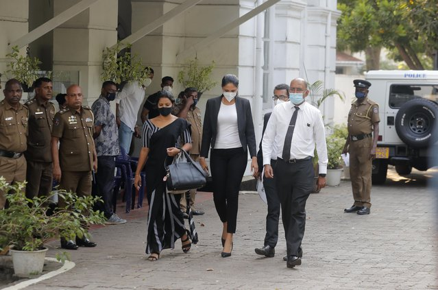 Mrs. World 2019 Caroline Jurie, center, leaves a police station after obtaining bail in Colombo, Sri Lanka, Thursday, April 8, 2021. Jurie's decision to remove the crown from the the winning Mrs. Sri Lanka contestant on stage moments after the winner was announced, because of claims she was a divorcee, drew widespread social media condemnation.  The winner Pushpika de Silva who was crowned again later had complained to police that her head was wounded when the clips of her crown were removed by Jurie. (Photo by Eranga Jayawardena/AP Photo)