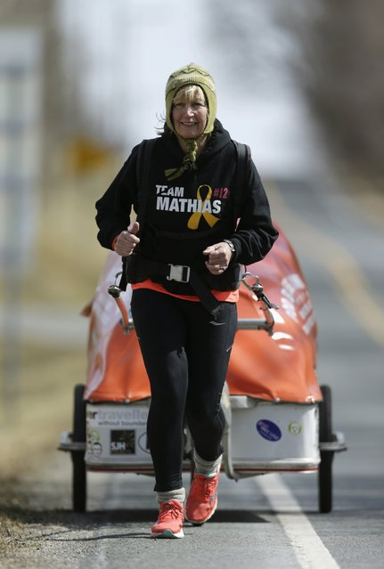 "Sixty-eight year old cross-country runner Rosie Swale-Pope runs on U.S. Route 50 while pulling her cart, ""The Icebird"", in Upperville, Virginia March 13, 2015. (Photo by Gary Cameron/Reuters)"