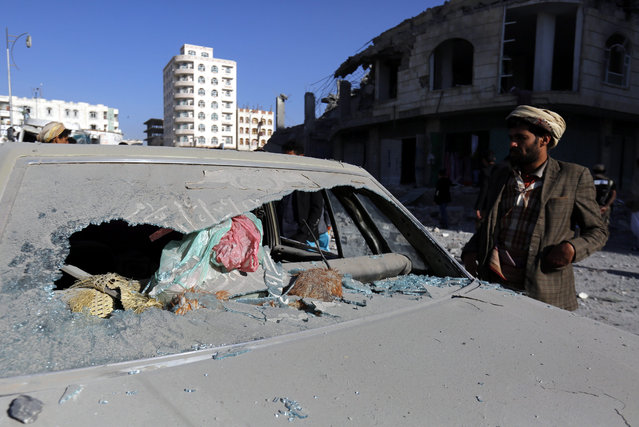 A Yemeni stands next to a car destroyed in a Saudi-led airstrike targeting a building of a senior Yemeni judge, in Sana'a, Yemen, 25 January 2016. According to reports, an airstrike carried out by the Saudi-led coalition targeted the building of Yemen's state security court judge Yahya Rubaid, killing him and six members of his family. (Photo by Yahya Arhab/EPA)
