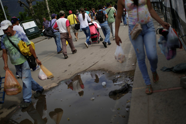People cross to Venezuela over the Simon Bolivar international bridge after shopping in Cucuta, Colombia December 1, 2016. (Photo by Marco Bello/Reuters)