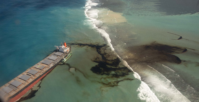 """This photo provided by the French Defense Ministry shows oil leaking from the MV Wakashio, a bulk carrier ship that recently ran aground off the southeast coast of Mauritius,, Sunday August 9, 2020. The Indian Ocean island of Mauritius has declared a """"state of environmental emergency"""" after the Japanese-owned ship that ran aground offshore days ago began spilling tons of fuel. (Photo by Gwendoline Defente/EMAE via AP Photo)"""