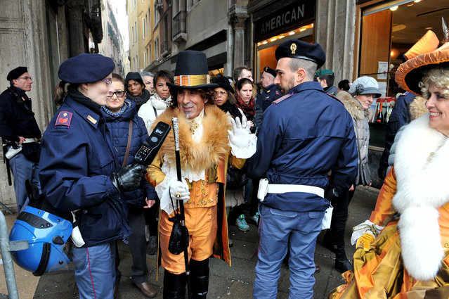 Police officers check a man wearing a carnival costume in Venice, Italy, Sunday, January 31 2016. (Photo by Luigi Costantini/AP Photo)
