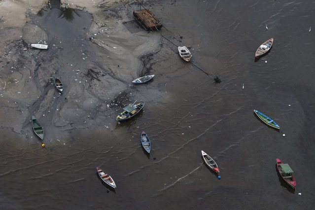 Small boats sit on the shore of Guanabara Bay near the suburb of Sao Goncalo, across the bay from Rio de Janeiro, Brazil, Monday, March 23, 2015. Authorities promised in Rio's winning bid to drastically clean up the pollution in Guanabara bay, cutting it by 80 percent. But with 500 days left before the games, experts say efforts have had little impact on the garbage and sewage pollution of the waters where sailing, swimming and other aquatic events will take place. (Photo by Felipe Dana/AP Photo)