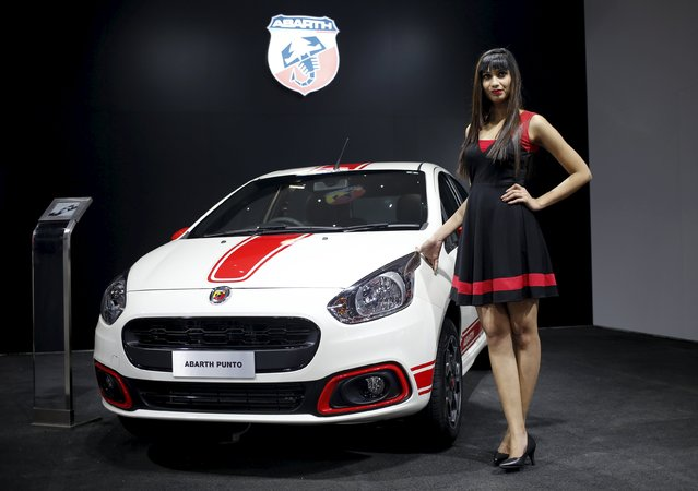 A model poses next to a Fiat Abarth car on display at the Indian Auto Expo in Greater Noida, on the outskirts of New Delhi, India, February 3, 2016. (Photo by Anindito Mukherjee/Reuters)