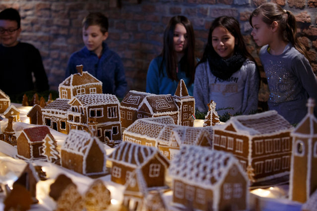 Visitors look at scale model of Szepetnek village made of gingerbread in Szepetnek, 220 kms southwest of Budapest, Hungary, 04 December 2018. The miniature gingerbread buildings created by using more than 20 kgs flour. The gingerbreads produced with traditional recipes are one of the sweet symbols of Christmas. (Photo by György Varga/EPA/EFE)
