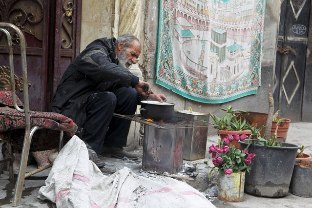A man cooks a meal using firewood in Aleppo, Syria January 22, 2016. (Photo by Abdalrhman Ismail/Reuters)