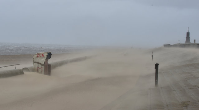 Strong winds blow sand over the beach of Cuxhaven-Doese at the Northern Sea, Germany Tuesday, March 31, 2014. (Photo by Carmen Jaspersen/AP Photo/DPA)