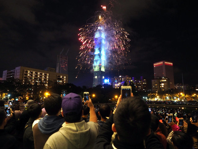 People make picture with their smartphones of fireworks and light effects that illuminate the night sky and the Taipei 101 skyscraper during New Year's Eve celebrations in Taipei, Taiwan, 01 January 2017. This year's cross-year celebration for the first time uses fireworks combined with light show displaying special effects around the building. (Photo by Henry Lin/EPA)