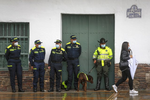 National Police wearing the force's new, blue uniforms stand by an officer wearing the old one, right with dog, as they stand guard on the sidelines of the ceremony presenting the new uniforms at Plaza de Bolivar in Bogota, Colombia, Monday, July 19, 2021. The uniforms changed from green to blue, and an arm patch features a QR code that allows anyone who scans it to see the officer's name, rank and badge number. (Photo by Ivan Valencia/AP Photo)