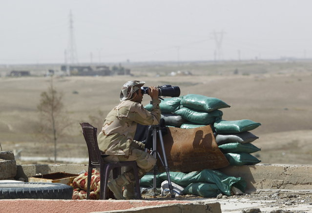 A member of the Iraqi security forces uses binoculars as he keeps watch in Tikrit, March 30, 2015. (Photo by Alaa Al-Marjani/Reuters)