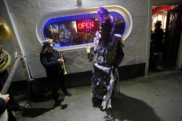 """Big Chief Kevin Goodman, right, of the Mardi Gras Indian tribe """"Flaming Arrows"""", talk to a member of the Elysian Brass Band, outside Buffa's Lounge, after members of the """"Societe des Champs Elysee"""" rode the Rampart-St. Claude street car line, which just opened last fall, to commemorate the official start of Mardi Gras season, in New Orleans, Friday, January 6, 2017. (Photo by Gerald Herbert/AP Photo)"""