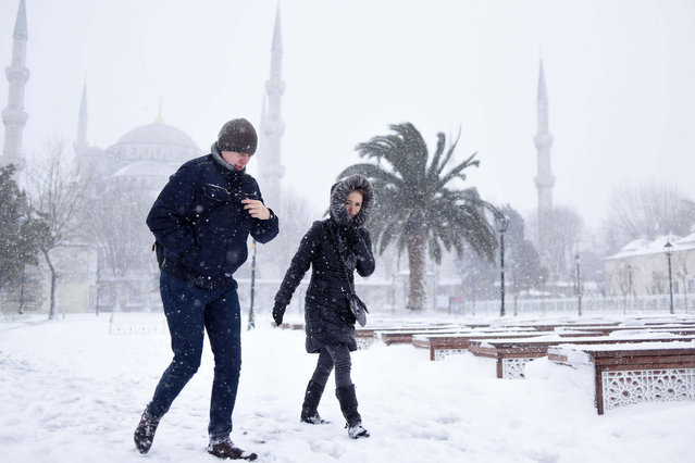 People walk in the snow, in the historic Sultanahmet district in Istanbul, Saturday, January 7, 2017. Heavy snow clogged roads, shipping traffic in Bosphorus and forced hundreds of flight cancellations in the Turkish metropolis. (Photo by Mert Akyol/Depo Photos via AP Photo)