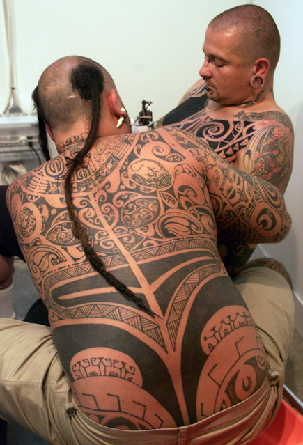 Pua, a tattoo artist from Tahiti, tattoos a man during the opening day of the IV International Tattoo festival in Madrid, June 2001. (Photo by Desmond Boylan/Reuters)