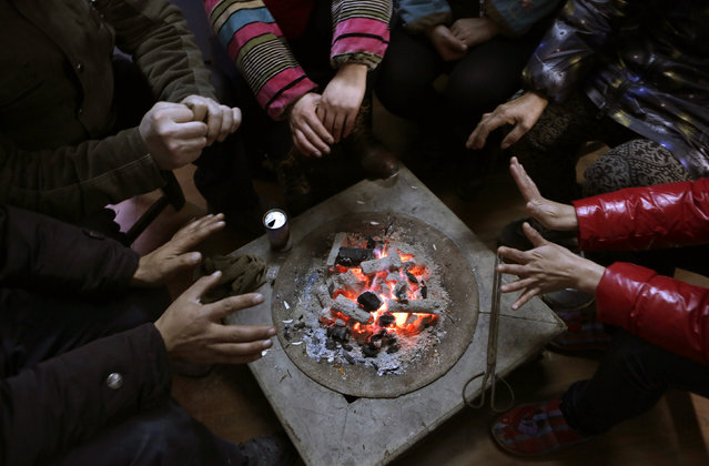 Local villagers get warm around a fire basket as they wait for a traditional ethnic Tujia wedding feast during celebrations marking the Lunar New Year, in Ziqiu town, Changyang county of China's Hubei province, February 14, 2016. (Photo by Jason Lee/Reuters)