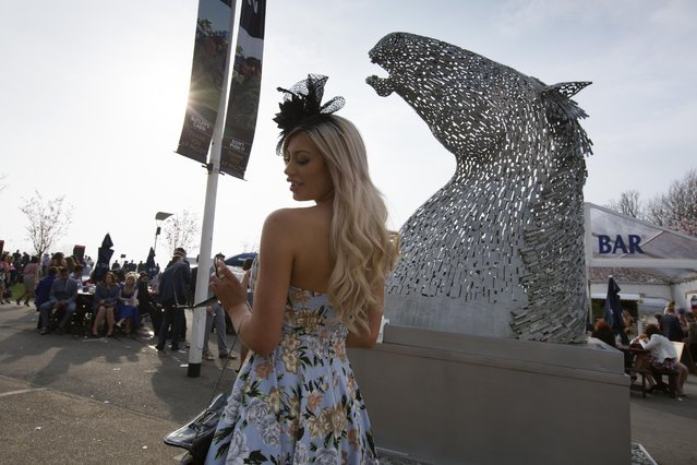 A race goer poses for pictures by a statue of a horse during Aintree race meeting's Ladies Day the day before the Grand National horse race at Aintree Racecourse Liverpool, England, Friday, April 10, 2015. (Photo by Jon Super/AP Photo)