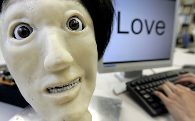 "A humanoid robot named Kansei, meaning ""sensibility"" in Japanese, makes a facial expression depicting ""happiness"", next to the word ""Love"" during a demonstration at a laboratory of Meiji University's Robot and Science Institute in Kawasaki, south of Tokyo in this June 4, 2007 file photo. (Photo by Yuriko Nakao/Reuters)"