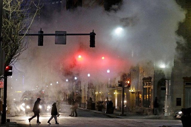 With temperatures nearing zero, a cloud of steam from a manhole blows across an intersection in downtown Pittsburgh during Monday's evening rush hour. The National Weather service is calling for a temperature of -11 degrees overnight, with a high of 2 degrees on Tuesday. (Photo by Gene J. Puskar/Associated Press)