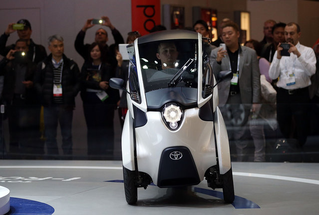 Attendees watch a demonstration of the Toyota i Road three-wheel electric vehicle at the Toyota booth at the 2014 International CES at the Las Vegas Convention Center on January 7, 2014 in Las Vegas, Nevada. CES, the world's largest annual consumer technology trade show, runs through January 10 and is expected to feature 3,200 exhibitors showing off their latest products and services to about 150,000 attendees. (Photo by Justin Sullivan/AFP Photo)