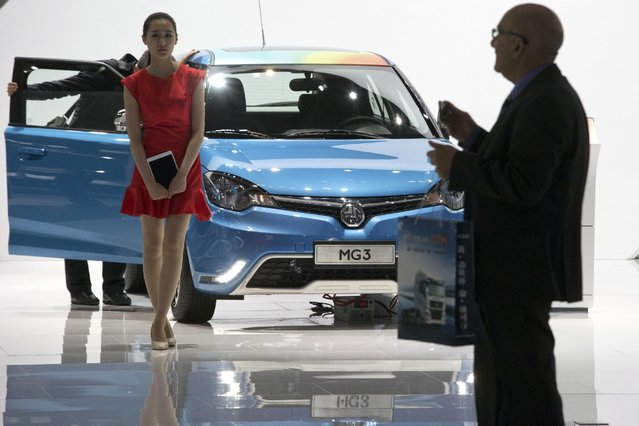 A Chinese woman waits to help attendee understand the MG3 on display at the Shanghai Auto Show in Shanghai, Monday, April 20, 2015. (Photo by Ng Han Guan/AP Photo)