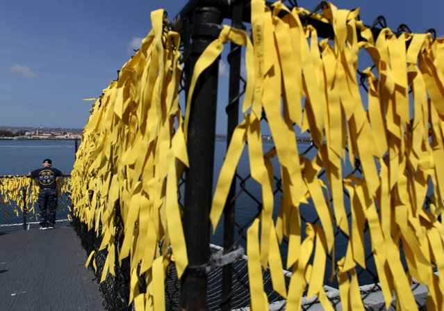 A U.S. veteran looks at some of the 58,300 yellow ribbons tied on a fence surrounding the Midway's flight deck to signify U.S. deaths in the Vietnam war as the Midway hosts a day-long ceremony commemorating the 40th Anniversary of Operation Frequent Wind and the fall of Saigon in San Diego, California, United States April 26, 2015. (Photo by Mike Blake/Reuters)