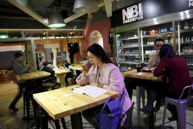 Customer Wang Wenqian drinks craft beer at microbrewery NBeer Pub in Beijing, China, March 6, 2016. (Photo by Kim Kyung-Hoon/Reuters)