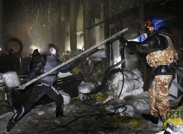 Protesters attack a government building in Kiev, on January 26, 2014. New violence erupted in Ukraine's capital during the night as a large crowd attacked a government exposition and conference hall where police were stationed inside. Early Sunday, demonstrators were throwing firebombs into the Ukrainian House building and setting off fireworks, and police responded with tear gas. (Photo by Sergei Grits/Associated Press)