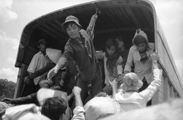 South Vietnamese refugees help others who have suffered the same plight to board a truck which will take them away from their endangered homes to a safe area in Vietnam on April 17, 1975. These Vietnamese left their native village south of Xuan Loc, an em-battled provincial capital in Long Khanh province east of Saigon, as government troops yielded ground to Communist forces. (Photo by AP Photo)