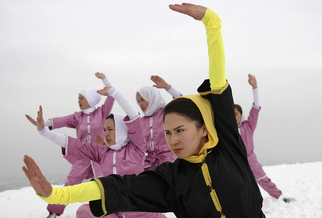 Shaolin martial arts students follow their trainer, Sima Azimi, 20, in black, during a practice session on a hilltop in Kabul, Afghanistan, Tuesday, January 25, 2017. The ten ethnic Hazara women and girls practice the martial arts of Shaolin on a hilltop in the west of Kabul. They are preparing for the day that Afghanistan can send its women's team to the Shaolin world championship in China. (Photo by Massoud Hossaini/AP Photos)