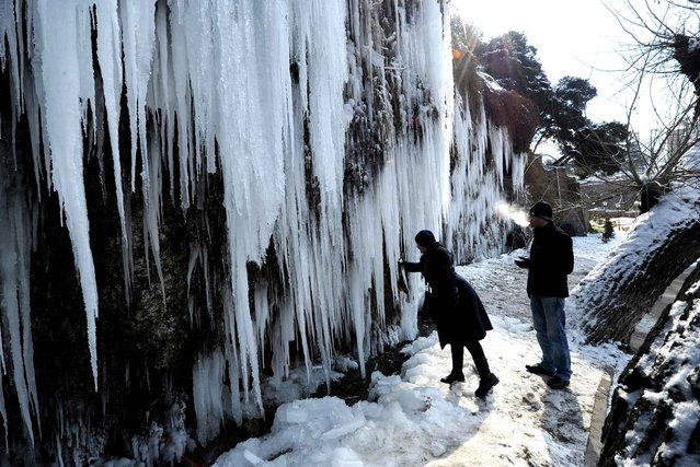 A women breaks off a small piece from the giant icicles on a rock in central Tbilisi, on February 3, 2014. The temperatures in the Georgia's capital dropped today to -7 C (19 F). (Photo by Vano Shlamov/AFP Photo)